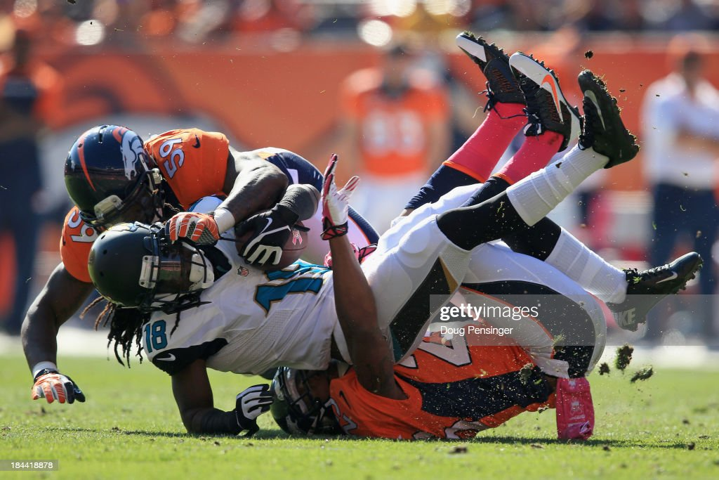 Wide receiver <a gi-track='captionPersonalityLinkClicked' href=/galleries/search?phrase=Ace+Sanders&family=editorial&specificpeople=7225920 ng-click='$event.stopPropagation()'>Ace Sanders</a> #18 of the Jacksonville Jaguars makes a reception and is tackled by cornerback Chris Harris #25 of the Denver Broncos and outside linebacker <a gi-track='captionPersonalityLinkClicked' href=/galleries/search?phrase=Danny+Trevathan&family=editorial&specificpeople=6475347 ng-click='$event.stopPropagation()'>Danny Trevathan</a> #59 of the Denver Broncos at Sports Authority Field at Mile High on October 13, 2013 in Denver, Colorado.