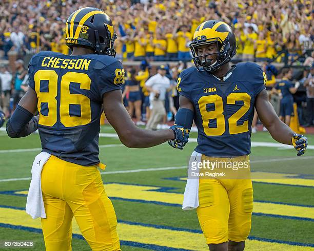 Wide receiver Amara Darboh of the Michigan Wolverines scores a first quarter touchdown and slaps hands with teammate wide receiver Jehu Chesson...