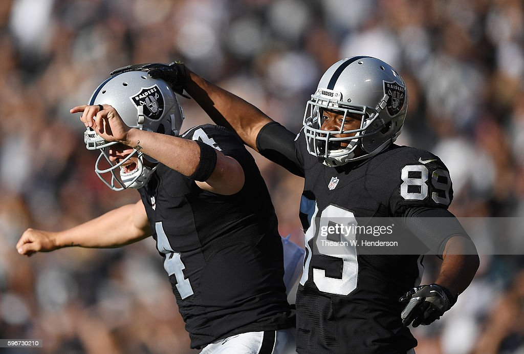 Wide receiver Amari Cooper #89 and quarterback Derek Carr #4 of the Oakland Raiders celebrates after Carr threw a touchdown pass to Cooper against the Tennessee Titans in the first half of their preseason football game at the Oakland Coliseum on August 27, 2016 in Oakland, California.