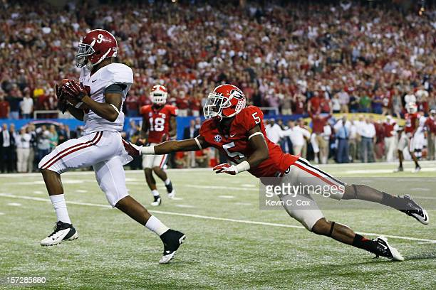 Wide receiver Amari Cooper of the Alabama Crimson Tide catches a fourth quarter touchdown pass in front of defensive back Damian Swann of the Georgia...