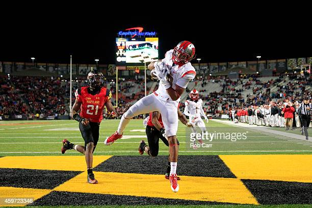 Wide receiver Andre Patton of the Rutgers Scarlet Knights catches a fourth quarter touchdown pass in front of defensive backs Sean Davis and William...