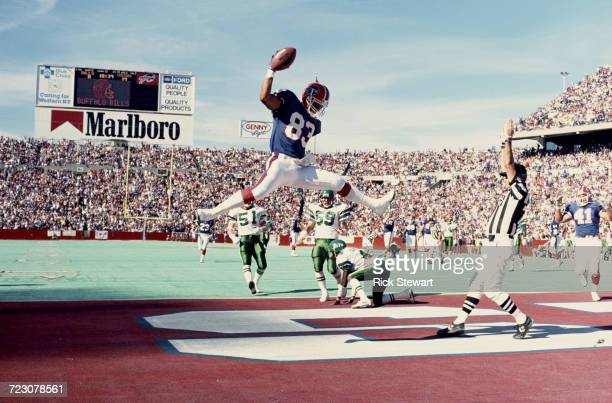 Wide receiver Andre Reed of the Buffalo Biils jumps in the air to celebrate scoring as the referee signals a touchdown during their AFC East football...