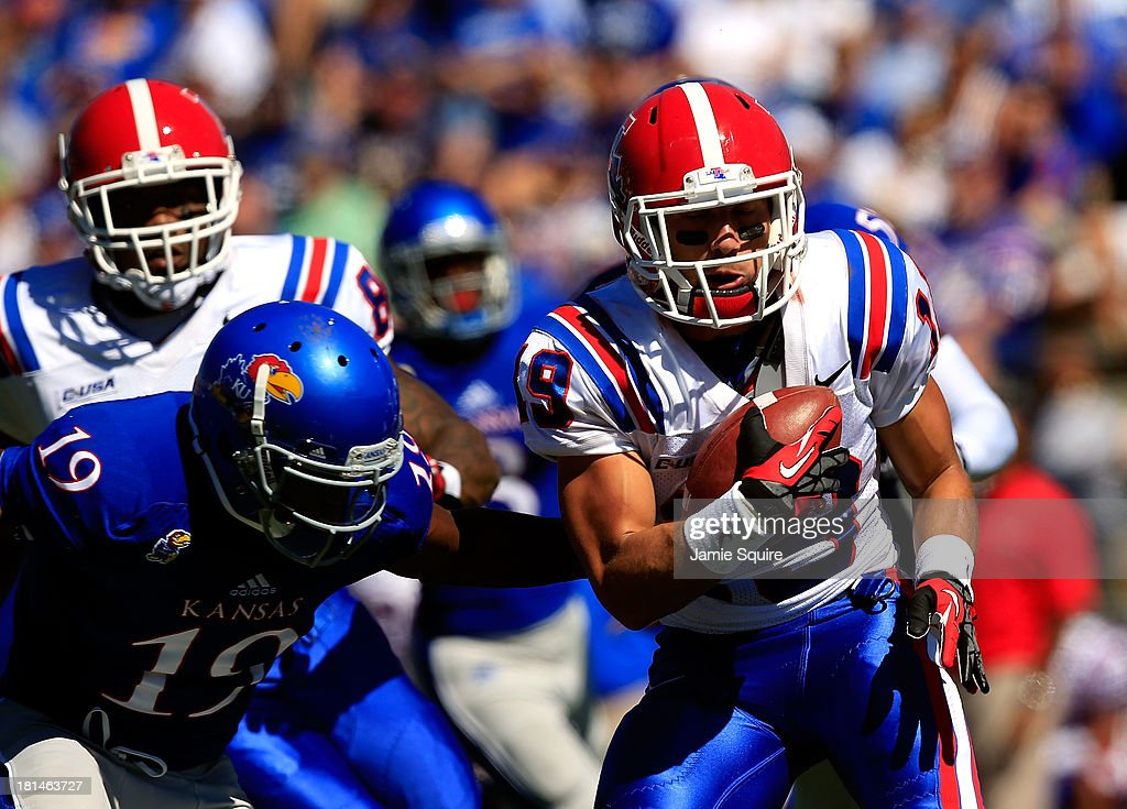Wide receiver Andrew Guillot #19 of the Louisiana Tech Bulldogs carries the ball as wide receiver Justin McCay #19 of the Kansas Jayhawks defends during the game at Memorial Stadium on September 21, 2013 in Lawrence, Kansas.