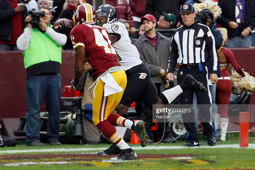 Wide receiver Anquan Boldin #81 of the Baltimore Ravens catches a touchdown pass in front of free safety Madieu Williams #41 of the Washington Redskins during the first half at FedExField on December 9, 2012 in Landover, Maryland.