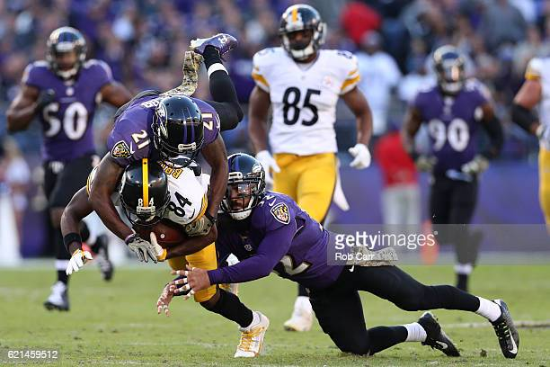 Wide receiver Antonio Brown of the Pittsburgh Steelers is tackled by free safety Lardarius Webb and strong safety Eric Weddle of the Baltimore Ravens...