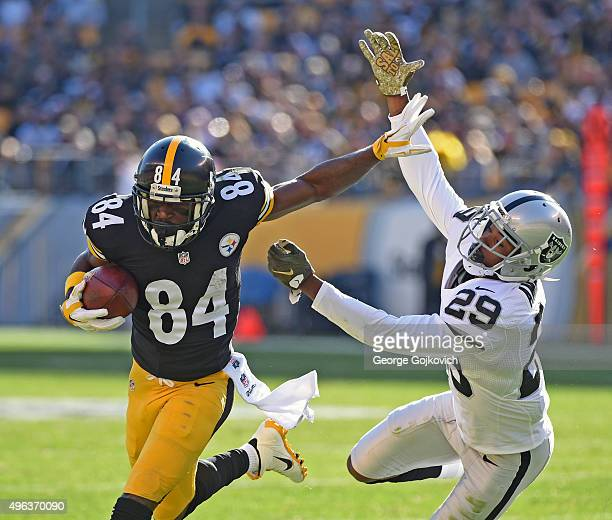Wide receiver Antonio Brown of the Pittsburgh Steelers tries to avoid the tackle of cornerback David Amerson of the Oakland Raiders during a game at...