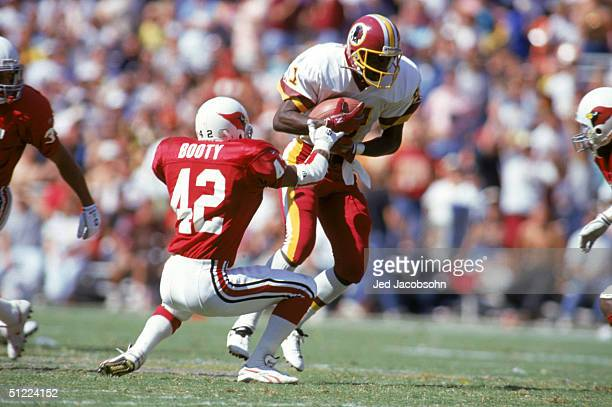 Wide receiver Art Monk of the Washington Redskins protects the ball as he breaks a tackle by safety John Booty of the Phoenix Cardinals during a NFL...