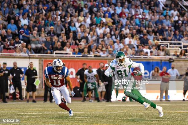 Wide receiver Bakari Grant of the Saskatchewan Roughriders runs with the ball against linebacker Chip Cox of the Montreal Alouettes during the CFL...