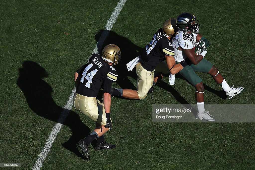 Wide receiver Bralon Addison #11 of the Oregon Ducks makes a reception as defensive back Jered Bell #21 of the Colorado Buffaloes makes the tackle and linebacker Addison Gillam #44 of the Colorado Buffaloes follows the play at Folsom Field on October 5, 2013 in Boulder, Colorado. The Ducks defeated the Buffs 57-16.