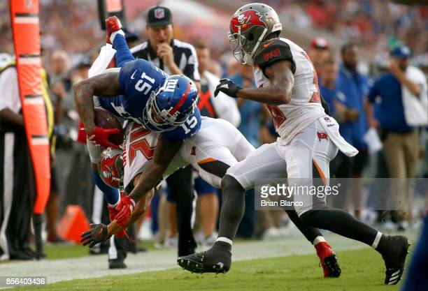 Wide receiver Brandon Marshall of the New York Giants is hit by cornerback Brent Grimes of the Tampa Bay Buccaneers during a carry in the second...
