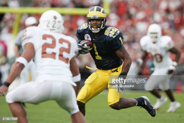 Wide receiver Braylon Edwards of the Michigan Wolverines runs with the ball under pressure from Phillip Geiggar of the Texas Longhorns in the 91st...