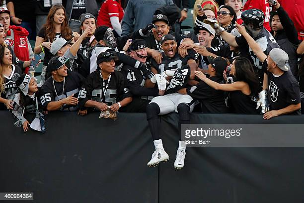 Wide receiver Brice Butler of the Oakland Raiders jump into the arms of fans in the Black Hole after defeating the San Francisco 49ers on December 7...