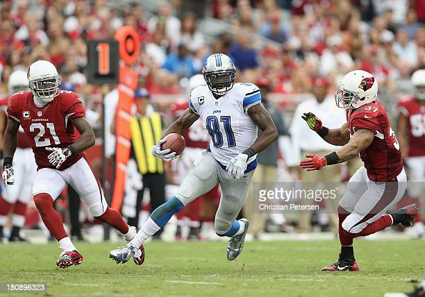 Wide receiver Calvin Johnson of the Detroit Lions runs with the football after a reception past strong safety Yeremiah Bell of the Arizona Cardinals...