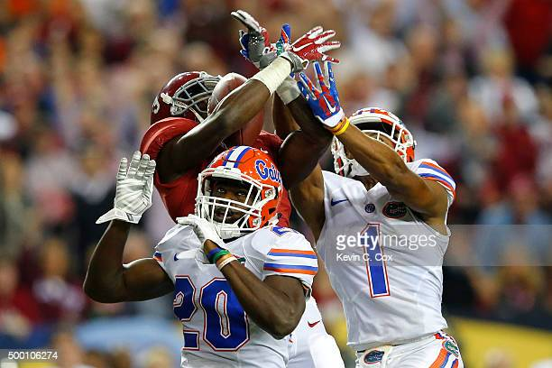 Wide receiver Calvin Ridley of the Alabama Crimson Tide receives the ball over defensive back Marcus Maye of the Florida Gators and defensive back...
