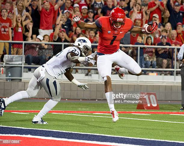 Wide receiver Cayleb Jones of the Arizona Wildcats catches a 22 yard touchdown pass while being covered by defensive back Nigel Haikins of the Nevada...