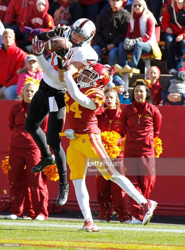 Wide receiver Charlie Moore #17 of the Oklahoma State Cowboys pulls in a pass for a touchdown as defensive back Nigel Tribune #34 of the Iowa State Cyclones defends in the first half of play at Jack Trice Stadium on October 26, 2013 in Ames, Iowa.