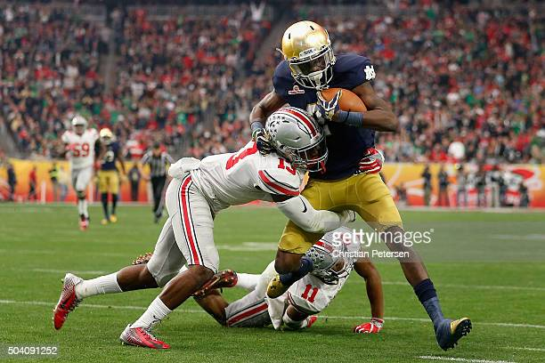 Wide receiver Chris Brown of the Notre Dame Fighting Irish runs with the football against safety Vonn Bell of the Ohio State Buckeyes and cornerback...