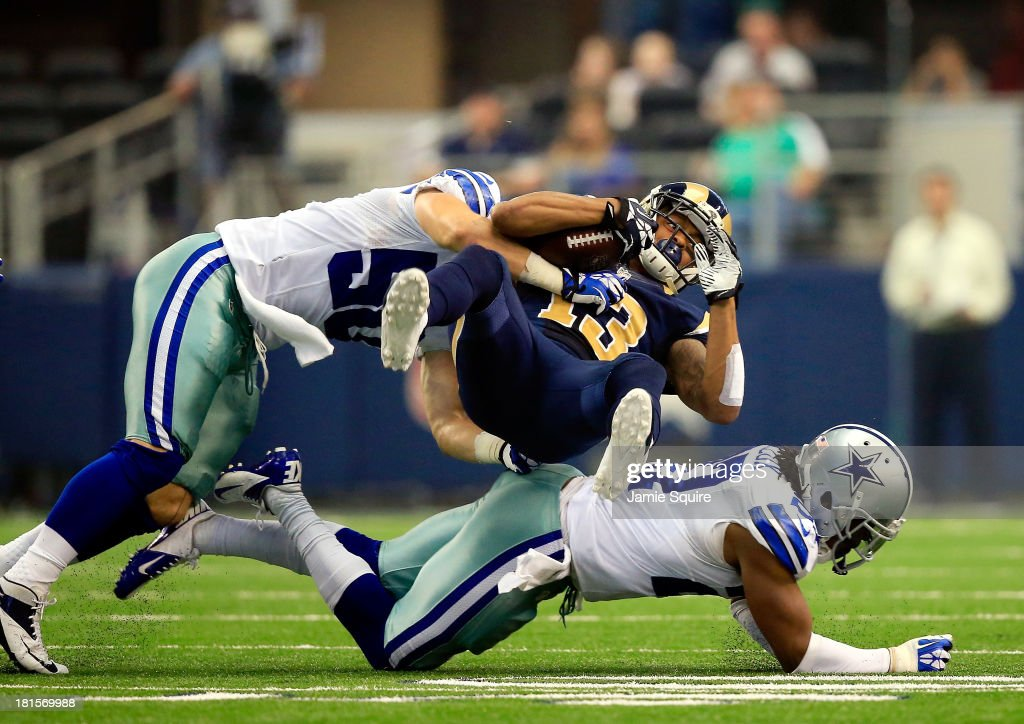 Wide receiver Chris Givens of the St Louis Rams is brought down by middle linebacker Sean Lee and defensive back JJ Wilcox of the Dallas Cowboys...