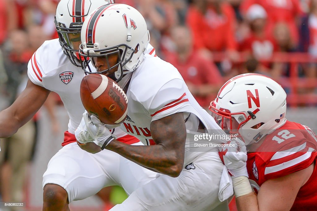 Wide receiver Christian Blake #4 of the Northern Illinois Huskies bobbles and recovers the ball while tackled by linebacker Luke Gifford #12 of the Nebraska Cornhuskers at Memorial Stadium on September 16, 2017 in Lincoln, Nebraska.