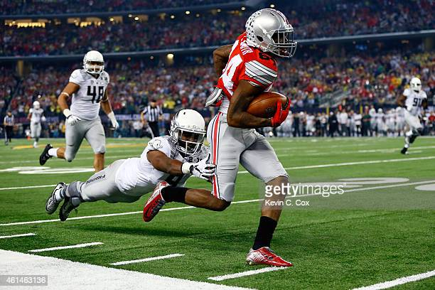 Wide receiver Corey Smith of the Ohio State Buckeyes dodges Reggie Daniels of the Oregon Ducks before fumbling the ball in the second quarter during...