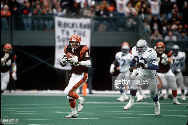 Wide receiver Cris Collingsworth of the Cincinnati Bengals is chased by linebacker Dave Wyman of the Seattle Seahawks after making a catch during an...