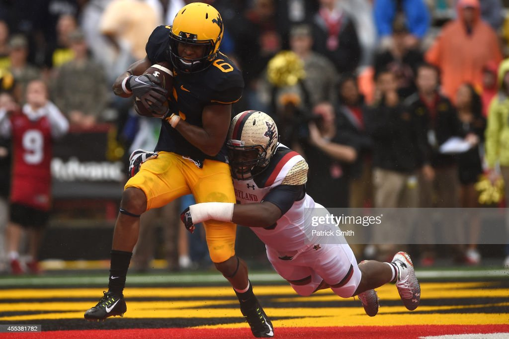 Wide receiver Daikiel Shorts of the West Virginia Mountaineers catches a touchdown pass in front of Jalen Brooks of the Maryland Terrapins in the...
