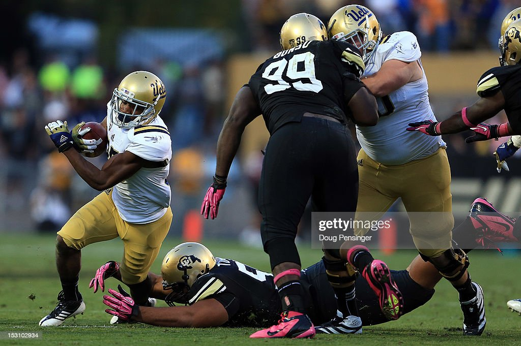 Wide receiver Damien Thigpen #25 of the UCLA Bruins is tackled by defensive lineman Josh Tupou #55 of the Colorado Buffaloes at Folsom Field on September 29, 2012 in Boulder, Colorado. UCLA defeated Colorado 42-14.