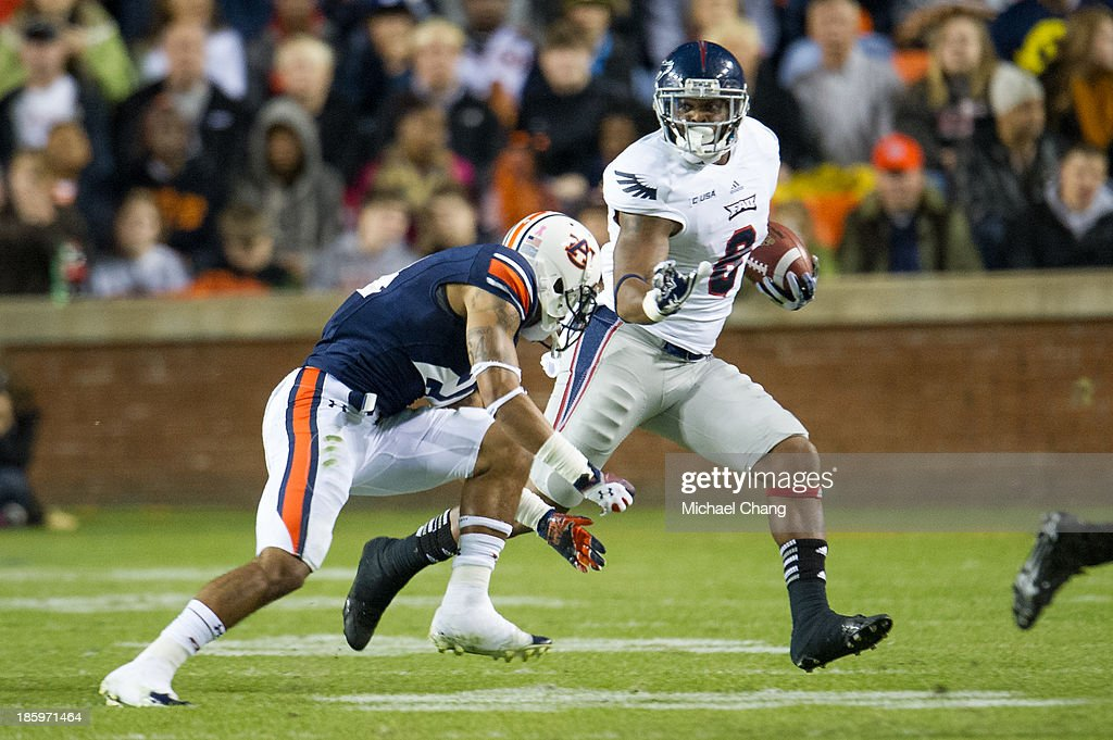Wide receiver Daniel McKinney #8 of the Florida Atlantic Owls looks to maneuver by defensive back Ryan Smith #24 of the Auburn Tigers on October 26, 2013 at Jordan-Hare Stadium in Auburn, Alabama. At the end of the first quarter Auburn leads Florida Atlantic 21-0.