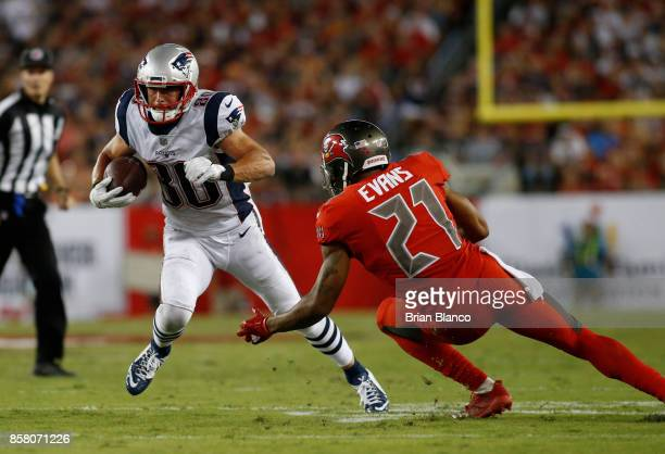 Wide receiver Danny Amendola of the New England Patriots avoids a tackle by safety Justin Evans of the Tampa Bay Buccaneers during a carry in the...