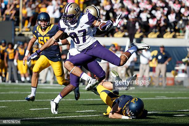 Wide receiver Dante Pettis of the Washington Huskies leaps over safety Patrick Worstell of the California Golden Bears during the second quarter of...