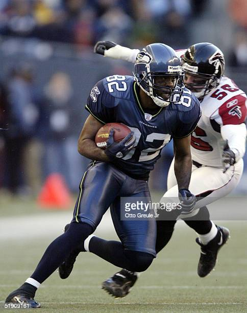 Wide Receiver Darrell Jackson of the Seattle Seahawks rushes against Keith Brooking of the Atlanta Falcons at Qwest Field on January 2 2005 in...