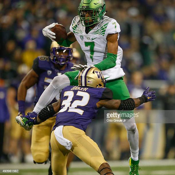 Wide receiver Darren Carrington of the Oregon Ducks hurdles defensive back Budda Baker of the Washington Huskies in the second half on October 17...