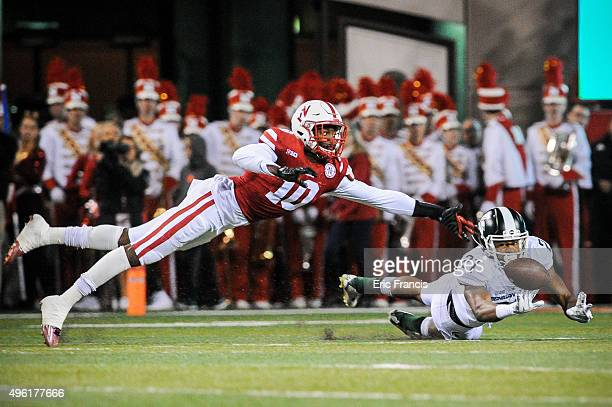 Wide receiver Davis Lewandowski of the Michigan State Spartans and defensive back Joshua Kalu of the Nebraska Cornhuskers dive for a ball during...