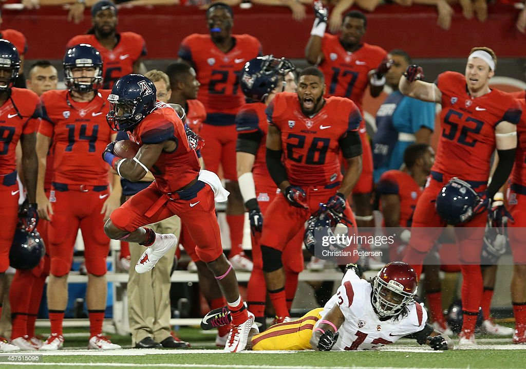 Wide receiver <a gi-track='captionPersonalityLinkClicked' href=/galleries/search?phrase=Davonte%27+Neal&family=editorial&specificpeople=9725369 ng-click='$event.stopPropagation()'>Davonte' Neal</a> #19 of the Arizona Wildcats runs with the football past cornerback Kevon Seymour #13 of the USC Trojans during the college football game at Arizona Stadium on October 11, 2014 in Tucson, Arizona. The Trojans defeatred the Wildcats 28-26.