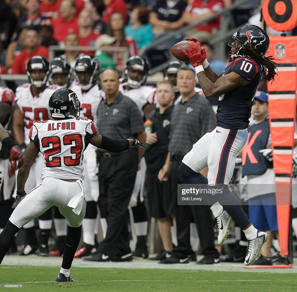 Wide receiver DeAndre Hopkins #10 of the Houston Texans completes a catch behind cornerback Robert Alford #23 of the Atlanta Falcons at Reliant Stadium on August 16, 2014 in Houston, Texas.