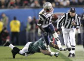 Wide receiver Deion Branch of the New England Patriots is pushed out of bounds at the 45 yard line after a 5 yard carry past Keith Adams of the...