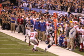 Wide Receiver Deion Branch of the New England Patriots makes a sideline catch and goes out of bounds against the New York Giants in Super Bowl XLVI...