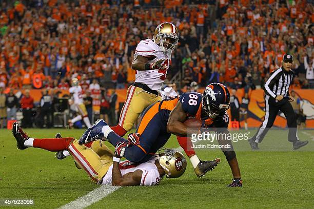 Wide receiver Demaryius Thomas of the Denver Broncos crashes over the goal line for a third quarter touchdown reception under coverage by cornerback...