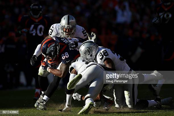 Wide receiver Demaryius Thomas of the Denver Broncos is hit by strong safety TJ Carrie outside linebacker Malcolm Smith and cornerback David Amerson...