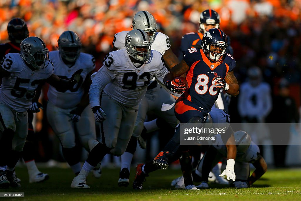 Wide receiver Demaryius Thomas of the Denver Broncos rushes for yards after a catch of a tipped ball and is pursued by defensive tackle Leon Orr of...