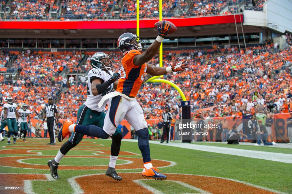 Wide receiver Demaryius Thomas #88 of the Denver Broncos scores a third quarter touchdown under coverage by cornerback Bradley Fletcher #24 of the Philadelphia Eagles at Sports Authority Field Field at Mile High on September 29, 2013 in Denver, Colorado.