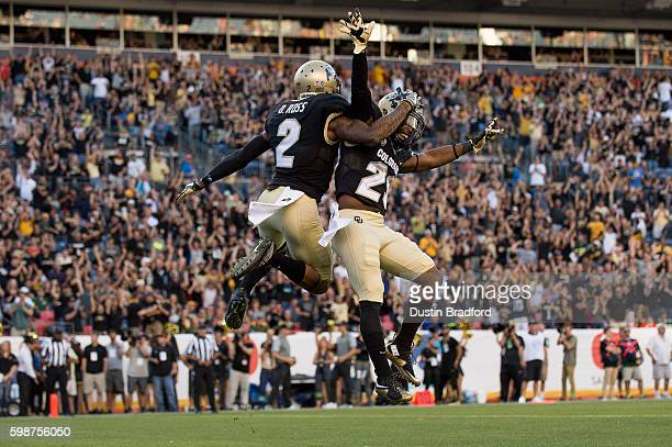 Wide receiver Devin Ross of the Colorado Buffaloes celebrates with running back Donovan Lee after scoring a first quarter touchdown against the...