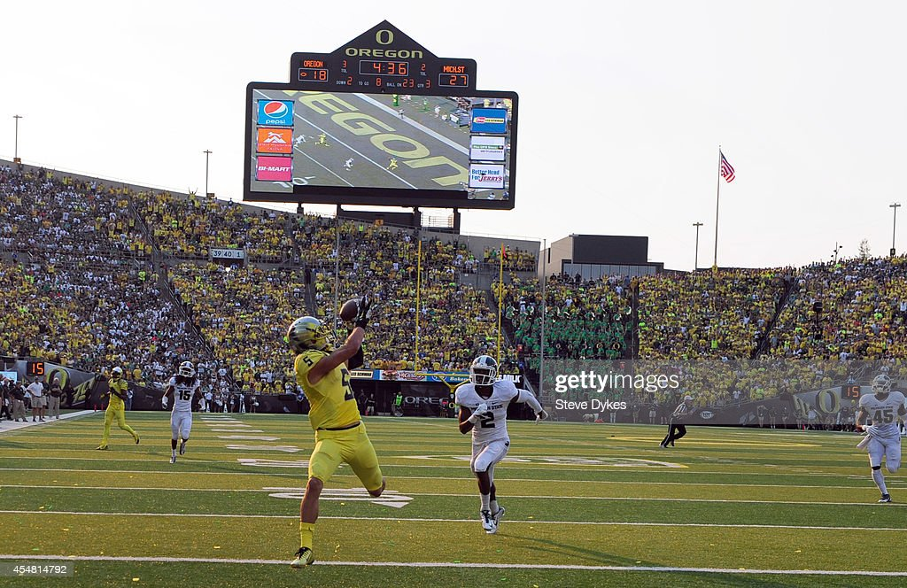 Wide receiver Devon Allen of the Oregon Ducks catches a touchdown pass in front of cornerback Darian Hicks of the Michigan State Spartans during the...