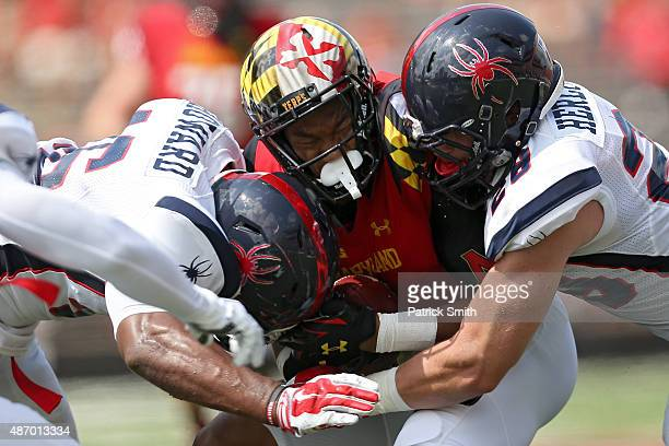 Wide receiver DJ Moore of the Maryland Terrapins is tackled by defensive back David Herlocker and linebacker Omar Howard of the Richmond Spiders in...