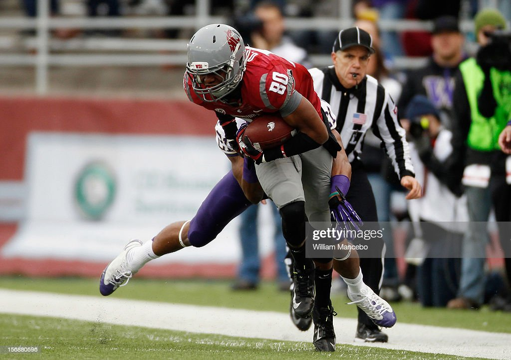 Wide receiver Dominique Williams #80 of the Washington State Cougars is tackled while during a game against the Washington Huskies at Martin Stadium on November 23, 2012 in Pullman, Washington.