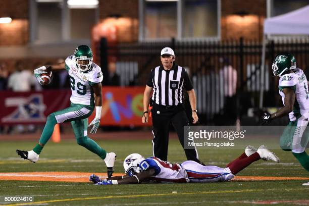 Wide receiver Duron Carter of the Saskatchewan Roughriders sidesteps a tackle from linebacker Chris Ackie of the Montreal Alouettes in the second...