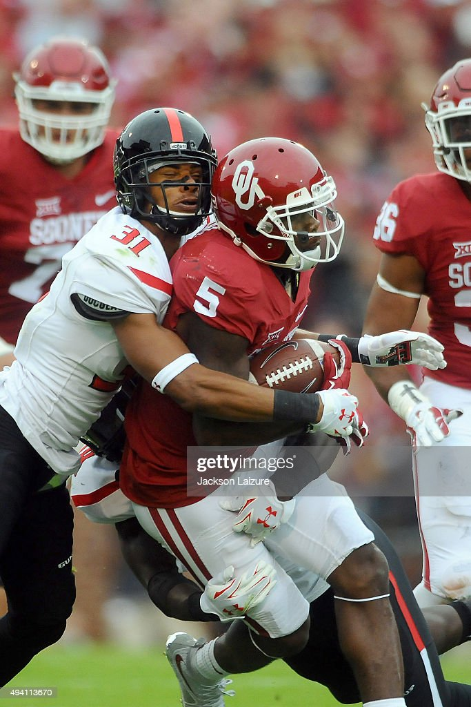 Wide receiver Durron Neal #5 of the Oklahoma Sooners gets tackled by defensive back Justis Nelson #31 of the Texas Tech Red Raiders on October 24, 2015 at the Gaylord Family Oklahoma Memorial Stadium in Norman, Oklahoma.