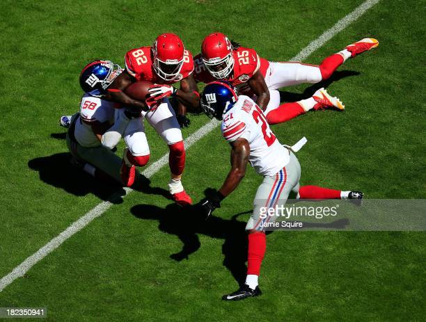 Wide receiver Dwayne Bowe of the Kansas City Chiefs is stopped by middle linebacker Mark Herzlich and free safety Ryan Mundy of the New York Giants...