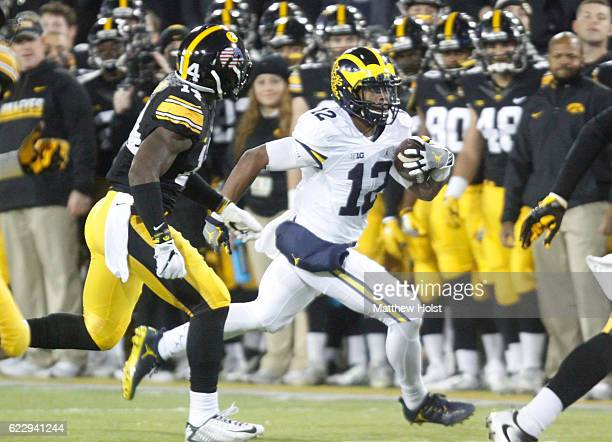Wide receiver Eddie McDoom of the Michigan Wolverines rushes up field during the second quarter past defensive back Desmond King of the Iowa Hawkeyes...