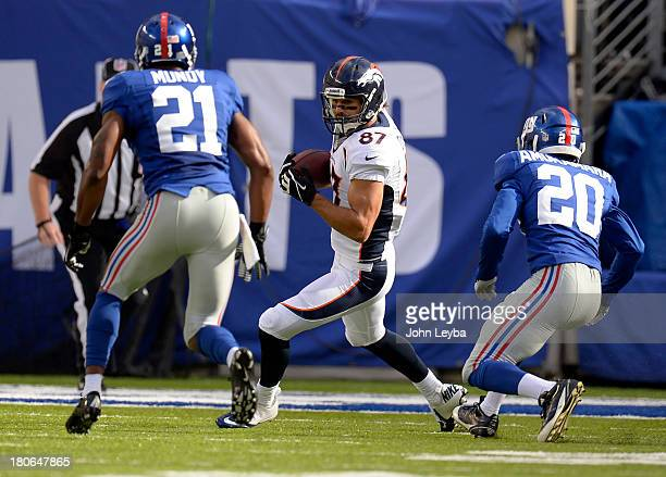wide receiver Eric Decker of the Denver Broncos turns up field after a catch as free safety Ryan Mundy of the New York Giants and cornerback Prince...